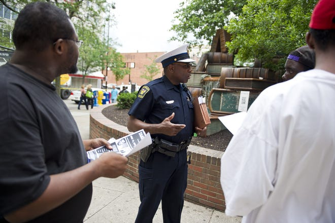 Cincinnati Police Officer Louis Arnold Sr. is president of the Sentinal Police Association. Here he works with youths outside the Public Library of Cincinnati and Hamilton County, Downtown.