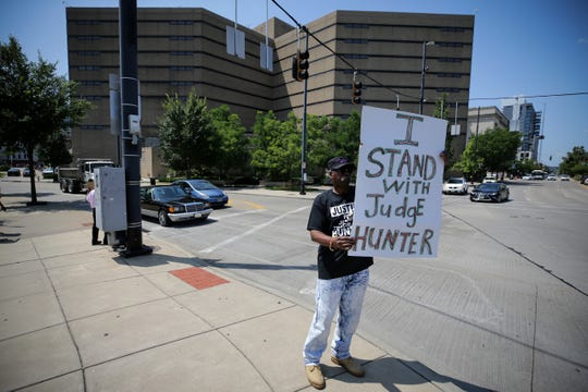 A man, who declined to give his name, protests he incarceration of former Hamilton County Judge Tracie Hunter, Thursday, July 25, 2019, at the intersection of Eggleston and Central Avenue in Cincinnati. Hunter was sentenced to six months in jail on Monday.