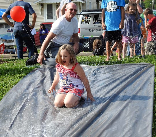 Jim Eckelberry helped children like Ella Lawson, 7, go down a slip-and-slide during a family friendly event Thursday at Himebaugh Park put on by Coshocton County Fatherhood Initiative.