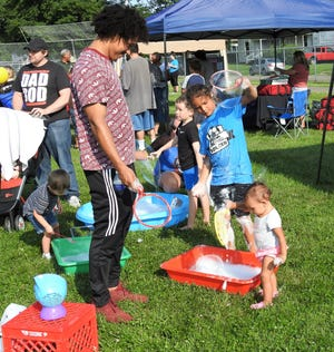 Keith Corbitt plays with his children, Keylan, 7, and Kovelynn, 1, at a bubbles station Thursday during a family fun night at Himebaugh Park put on by the Coshocton County Fatherhood Initiative.