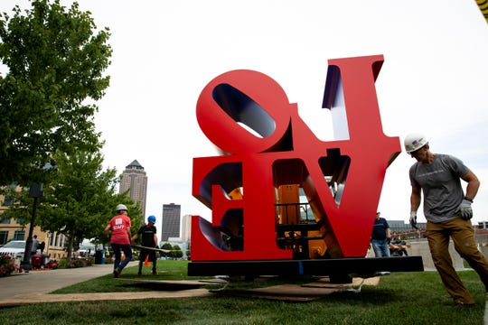 """Chief Preparator Jay Ewart with the Des Moines Arts Center helps install an edition of Robert Indiana's """"LOVE"""" at the Pappajohn Sculpture park on Thursday, July 25, 2019 in Des Moines."""