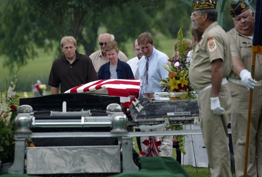 A Veterans of Foreign Wars post color guard presents a 21-gun salute and plays taps for Lori Duncan, who was a Navy veteran, at Elmwood Cemetery in Mason City, Iowa, on July 10, 2004. Dustin Honken was convicted in the killing of Duncan, her two daughters and two others.