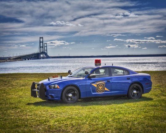 A Michigan State Police car in front of the Mackinac Bridge.