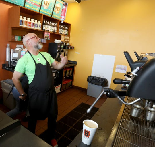 Mike McFall, co-CEO of Biggby Coffee, shows off an old trick from his days as a barista. McFall visited the Biggby location on 9 Mile in Farmington Hills, Michigan on Friday, July 19, 2019.
