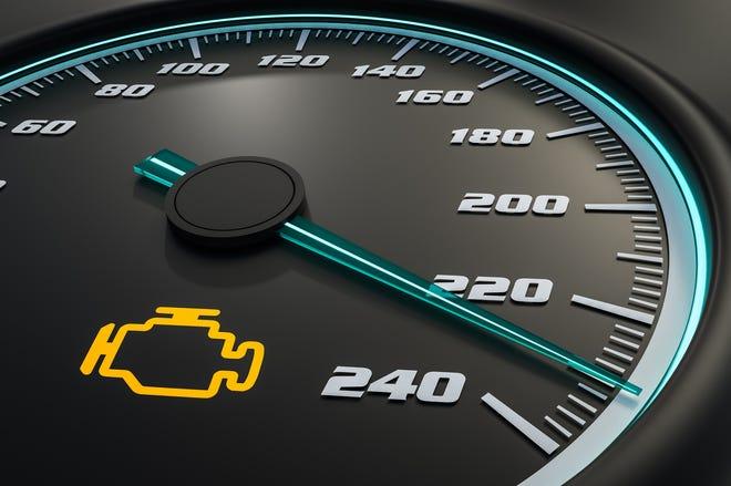 Engine check light on car dashboard.