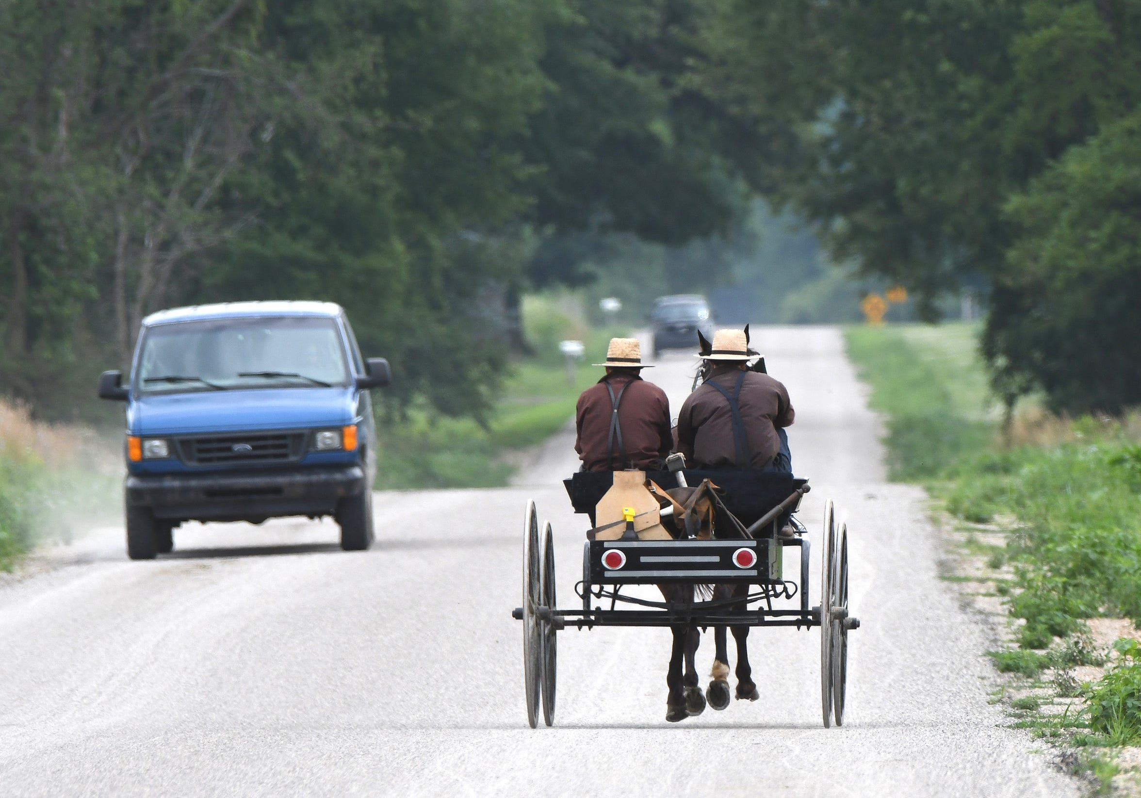 A horse-drawn buggy shares the road with motor vehicles along E. Southern Road in California Township, Michigan.