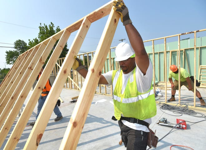 Manic Construction Inc. employee Thomas Harper of Detroit helps to raise wall framing for North Pine Street Homes, a development by nonprofit Oakland Housing in Detroit's North Corktown.