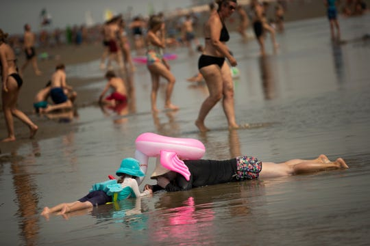 People cool off during a hot summer day at the beach in De Haan, Belgium on Thursday.