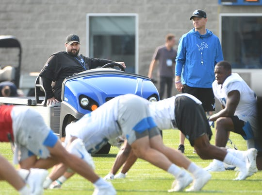 Lions head coach Matt Patricia, who is recovering from leg surgery, and offensive coordinator Darrell Bevell watch over practice.