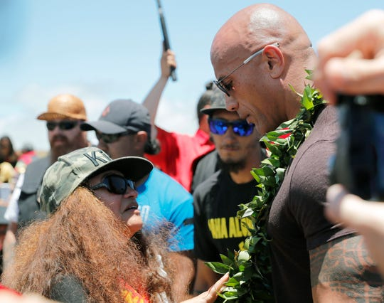 "Actor Dwayne ""The Rock"" Johnson, right, is greeted by community leader Pua Case during a visit to the protest site on Wednesday."