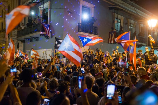 People celebrate outside the governor's mansion La Fortaleza, after Gov. Ricardo Rossello announced that he is resigning Aug. 2 after nearly two weeks of protests and political upheaval touched off by a leak of crude and insulting chat messages between him and his top advisers, in San Juan, Puerto Rico, Thursday, July 25, 2019.