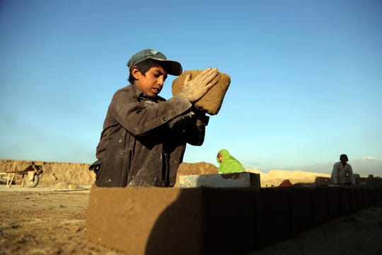 In this Wednesday, June 19, 2019, photo, Kamran, 10, works at a brick factory on the outskirts of Kabul, Afghanistan. Every day before dawn, 10-year-old Kamran goes to work with his father and other relatives at a brick factory on the outskirts of Kabul.