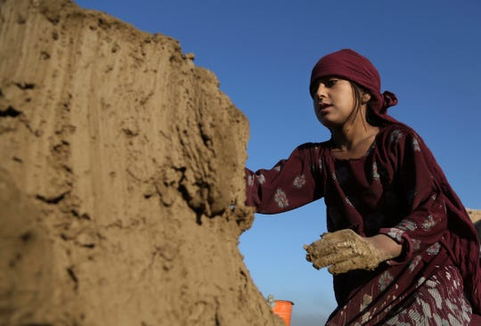 In this Wednesday, June 19, 2019, photo, Hameda, 8, works at a brick factory on the outskirts of Kabul, Afghanistan. The U.S. and its allies have sunk billions of dollars of aid into Afghanistan since the invasion to oust the Taliban 18 years ago, but the country remains mired in poverty.