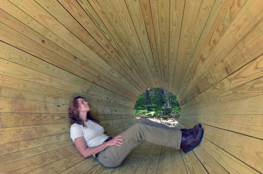 Anne Fleming, Director of Communications for the Little Traverse Conservancy, sits in a huge 10-foot wood megaphone in the Boyd B. Barnwell Family Preserve near Afton, Mich. Monday, July 22, 2019. The megphone amplifies the sounds of the surrounding forest and allows visitors to sit, relax and enjoy the unique device, believed to be the only one in the United States.