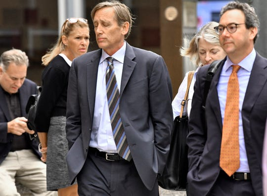 Jeffrey Bizzack, center, arrives at federal court with members of his defense team, Wednesday July 24, 2019, in Boston where he is expected to plead guilty to charges for allegedly paying to get his son into the University of Southern California as a fake volleyball recruit.