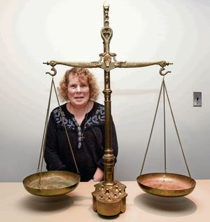 Cindy Sloan of Shelby Township shows off an old balance scale during the Trash or Treasure appraisal event.