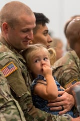 CPT William Bland holds his daughter Aaliyah Bland during the 206th Engineer Battalion Departure Ceremony Thursday, July 25, 2019.