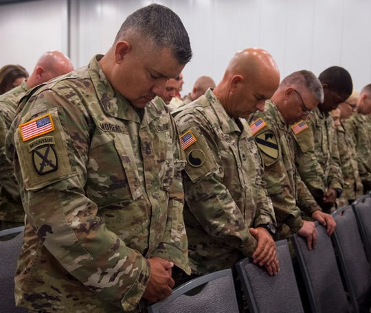 Soldier with the 206th Engineer Battalion pray during their departure ceremony at the Owensboro Convention Center Thursday, July 25, 2019.