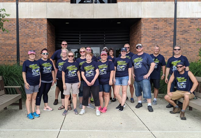 Faculty, staff and administration proudly presenting their Campus Cleanup Day shirts after a day working in the heat.