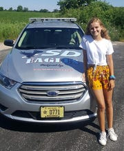 Abigail Neubauer poses next to the Southern Door School District resource officer's car she designed.