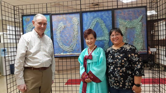 "INFINITI Guam recently hosted the ""Moving Colors, Series 5 — Chamorro Seascapes II"" art exhibit at its Upper Tumon showroom, which features the art of manåmko' from the Guam Gine 'fli'e Center in Dededo, according to INFINITI Guam General Manager Philippe Gerling. Pictured with Yeon Sook Park is Gerling and Dededo Mayor Melissa Savares."