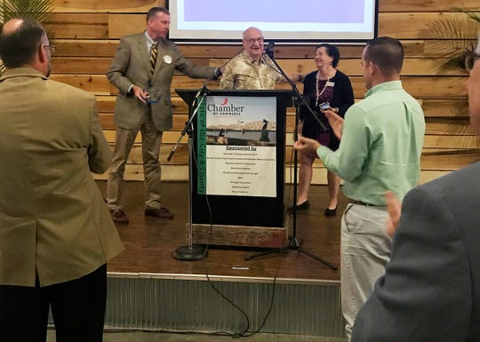 The Kyndle luncheon audience stands to applaud Bob Park (center) for being named Henderson Rotary Club's 2019 Hometown Hero recipient. On stage with him is Rotary President Mark Chumbler (center left) and award presenter Donna B. Stinnett (center right).