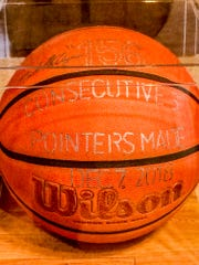 A basketball used by Mike Ayers, 63, to shoot 165 3-pointers in a row is preserved in a glass case at his home.