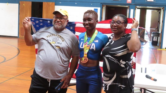 Pictured: Ijeyi Onah (center), her Ithaca High School track coach — John Baker, and her mother, Joy Onah