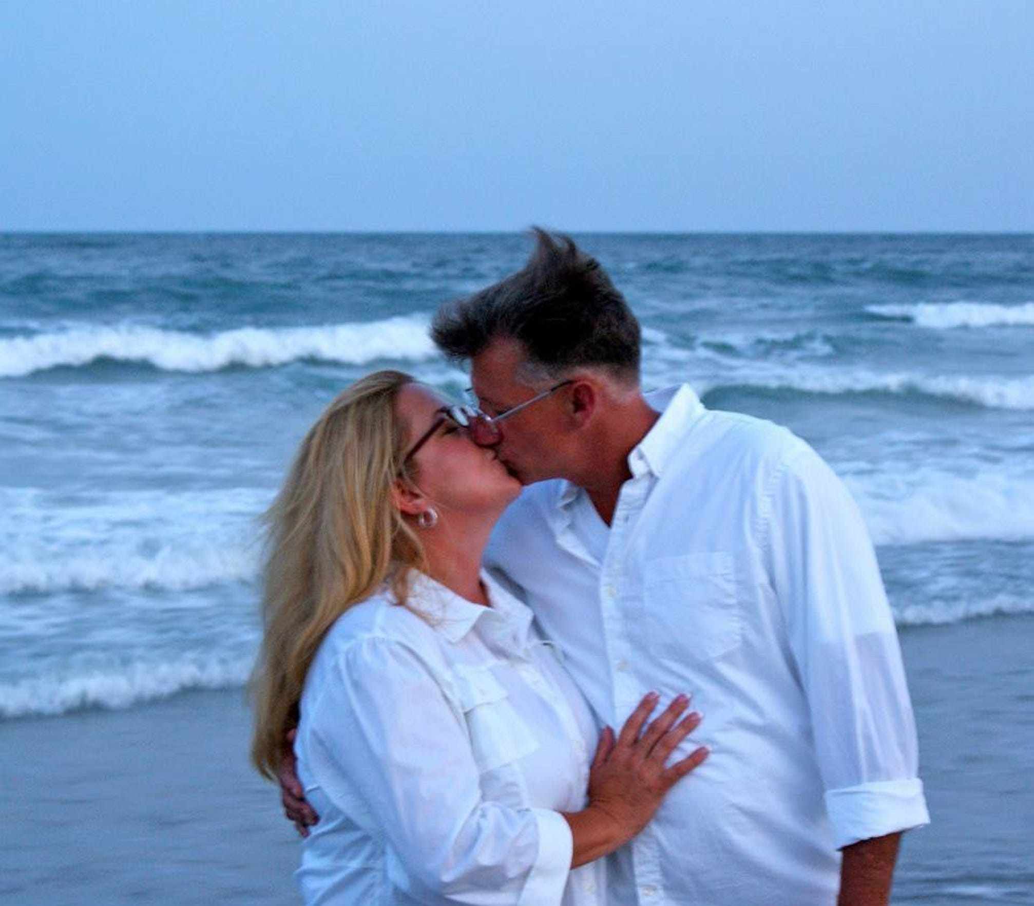 Julie and Fred Pepperman kiss for a photo on the beach during a vacation to Florida in 2018. Fred Pepperman, 53, died on July 14, after swimming out to rescue his daughters from a riptide at the Miramar Beach area.