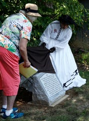Pam Allen, left, site manager for the Hanby House, and Cathy Nelson, founder and president emeritus of Friends of Freedom, remove a blanket covering a monument to runaway slaves who are buried in Pleasant Hill Cemetery in Rushville.