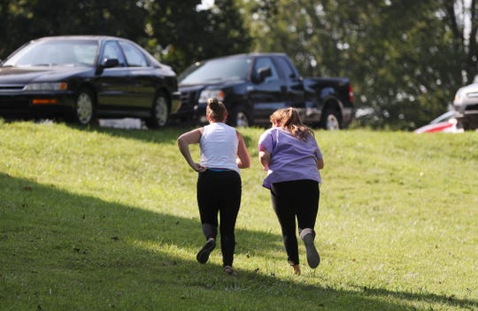Whitney Davis, left, and her cousin Tracy Davis ran off to the next location after checking their cellphones for coordinates while searching for $100 bills hidden in Cherokee Park.  A total of $2000 was hidden in $100 increments by Louisville's Breakout Games.  July 24, 2019