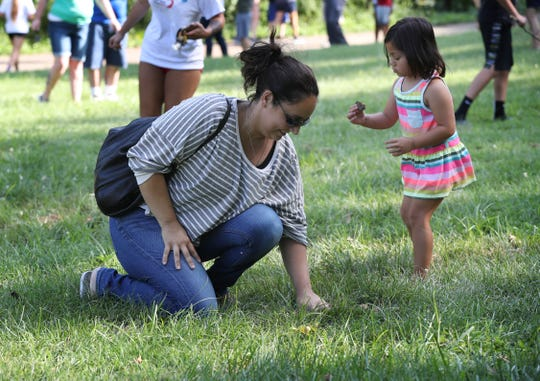 Patri Marconi and her daughter Alana Yin, 4, searched for $100 bills hidden in Cherokee Park.  A total of $2000 was hidden in $100 increments by Louisville's Breakout Games.  July 24, 2019