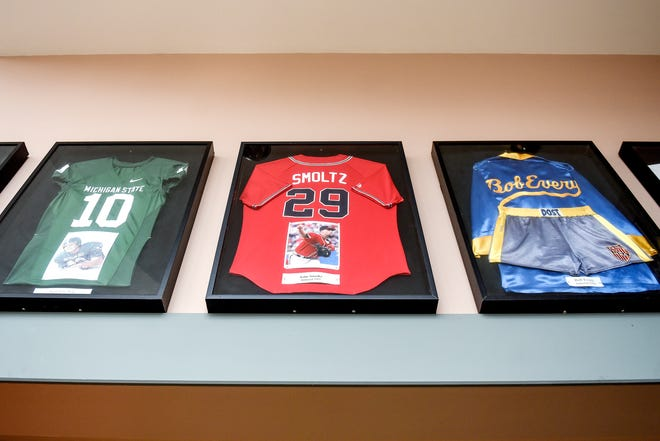 From left, jerseys from past inductees Brad Van Pelt, John Smoltz and boxing shorts and robe worn by Bob Every are on display in the lobby before the start of the Greater Lansing Area Sports Hall of Fame Induction Ceremony on Thursday, July 25, 2019, at the Lansing Center.