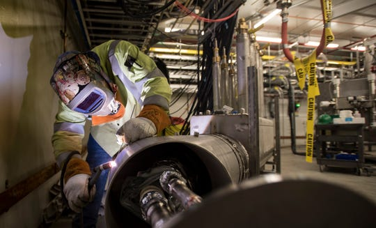 A welder works on specialized equipment inside the Facility for Rare Isotope Beams at Michigan State University on July 25.