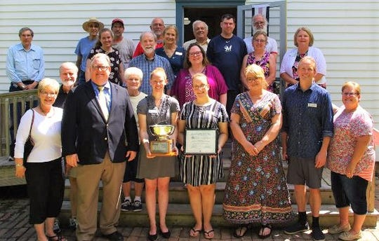 Members of the Manitowoc County Historical Society accept the Reuben Gold Thwaites Trophy, which is presented annually to a Wisconsin Historical Society. Christian Overland, Ruth & Hartley Barker Director of the Wisconsin Historical Society and Janet Seymour, Interim Director of Outreach of the Wisconsin Historical Society, presented the Manitowoc County Historical Society with the award.