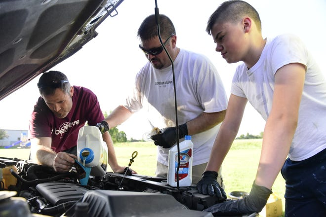 Men from Gospel Baptist Church in Galion change oil for single mothers Wednesday evening. From left are Pastor Steven Hodges, Chris Williams and Wyatt Williams, 11.