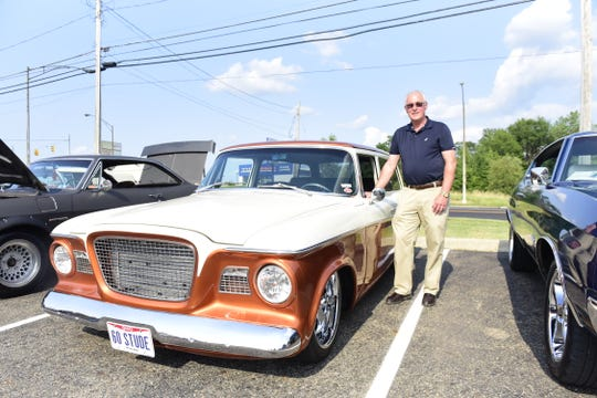 Scott Sharrock stands proudly next to his 1960 Studebaker during the weekly car show Thursday evening at the Pizza Hut in Ontario.