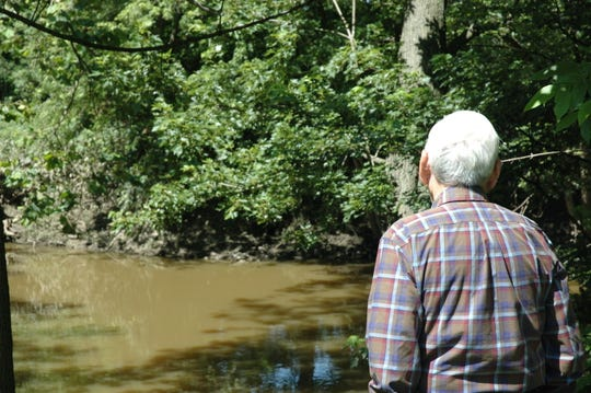 Clarence Greer, LCA member, examines the Scioto River in LaRue, just down river from where a new check valve will be installed to help mitigate flooding in the village.