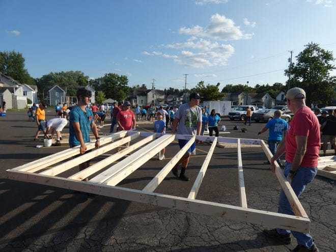 Ryan Meade, left, Joey Songer, middle, and Greg Clark, right, carry a wall Tuesday that will become part of a Habitat for Humanity house on Olney Avenue. Meade and Songer were among more than 40 Pleasant High School football players who volunteered at the Marion First Church of the Nazarene.