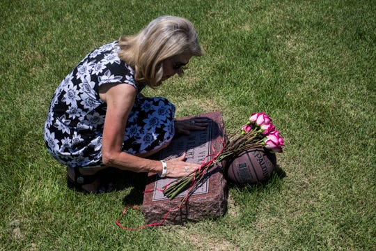 Gayle Rose, civic leader and a friend who also spoke at Wright's funeral, places flowers at Lorenzen Wright's grave Thursday afternoon, July 25, 2019.