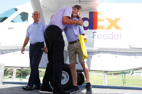 Reid Russell, 12, a St. Jude patient and son of a FedEx Express pilot, is hugged by ALSAC President and CEO Richard Shadyac Jr. during a ceremony in partnership between FedEx and St. Jude Children's Research Hospital naming a Cessna Caravan his honor at the WGC-FedEx St. Jude Invitational at TPC Southwind on Thursday, July 25, 2019.