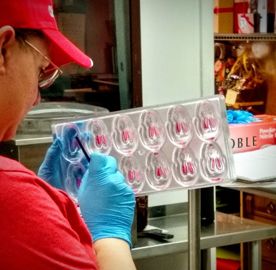 A chocolatier at The Chocolate Chisel shop hand pants each bunny ear pink in the mold before pouring the chocolate.