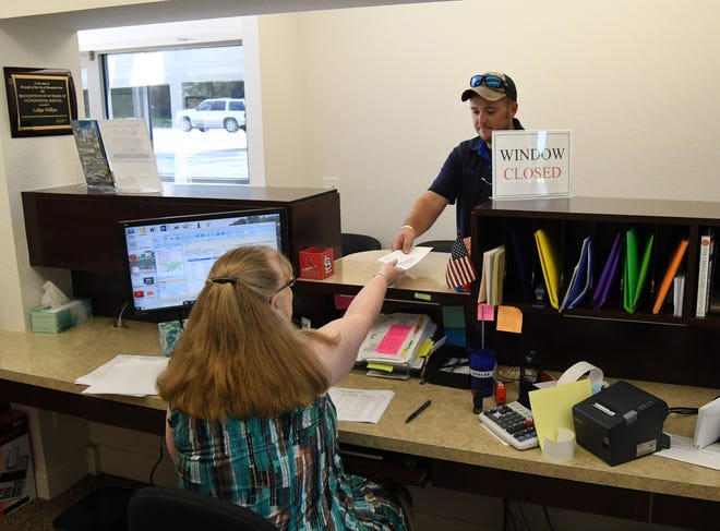 A Mountain Home Water Department customer drops off his bill at the water department front counter in this file photo. Beginning  today, the City of Mountain Home will close the Water Department lobby to the public but will keep its drive-thru window open to assist customers.