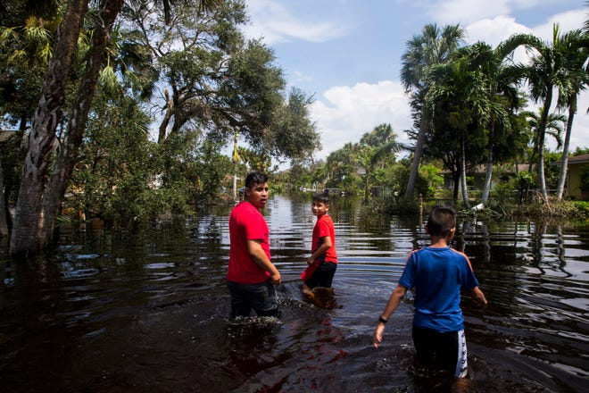 Manuel Angel, 11, from right, Ezequiel Manuel, 11, and Manuel Matea, 19, wade into flood waters to check on their house on Saunders Avenue in Bonita Springs on Thursday, Sept. 14, 2017, four days after Hurricane Irma.