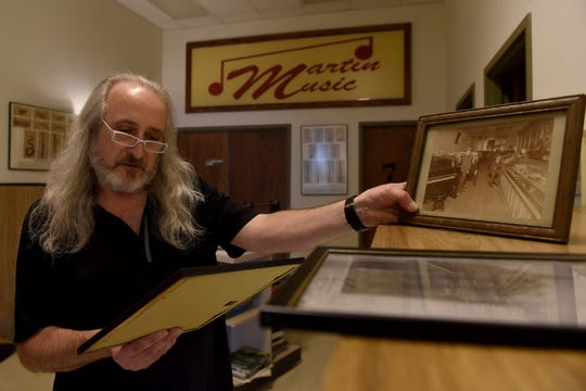 President and CEO Doug Baker shows photos and newspaper articles from throughout Martin Music's 71 year history selling and repairing instruments, musical equipment and hosting music lessons in Newark.