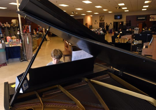 Jacob Bishop, 11, plays the Jurassic Park theme song on one of pianos in the display room of Martin Music on 21st Street in Newark. Martin Music, which has been in business for 71 years, is planning to close its doors July 31.