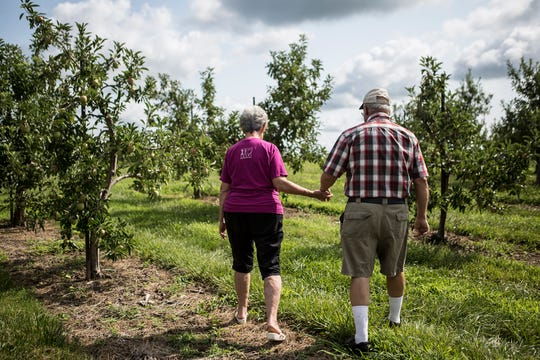 Penny and Mitch Lynd walk hand-in-hand through their apple orchard. Mitch's grandfather purchased the farm 100 years ago.