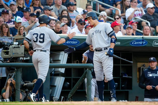 Jul 24, 2019; Minneapolis, MN, USA; New York Yankees outfielder Aaron Judge (99) congratulates outfielder Mike Tauchman  (39) after scoring in the second inning against Minnesota Twins at Target Field. M