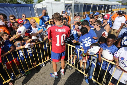 Eli Manning signs autographs for fans after the first practice of the season. Thursday, July 25, 2019