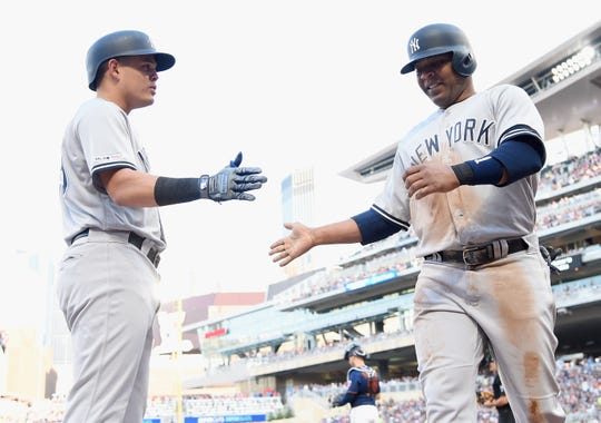 Gio Urshela, left, of the New York Yankees congratulates teammate Edwin Encarnacion on scoring a run against the Minnesota Twins during the second inning of the game on July 24, 2019 at Target Field in Minneapolis, Minnesota.
